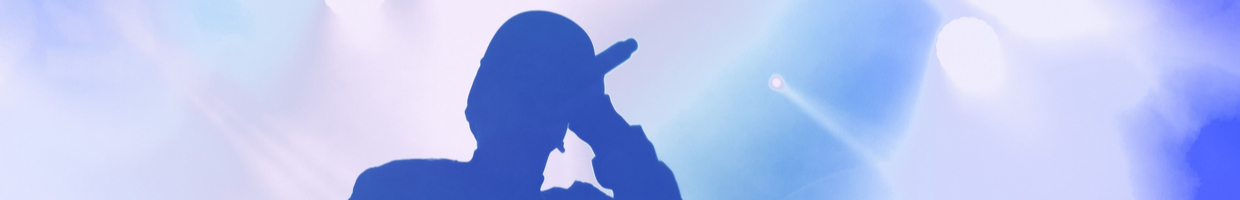 A silhouette of a singer performing with a blue background.