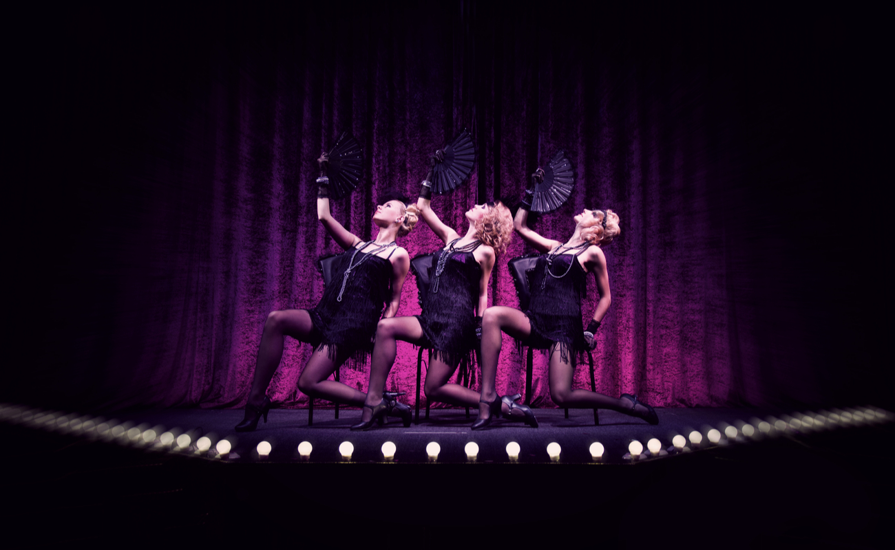 Three women in black dresses holding fans perform on stage with a purple curtain backdrop.
